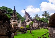 Het reuzestandbeeld die van Boedha op groen gras met omringend s liggen stock fotografie