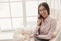 Het richten van het Aziatische vrouw vertellen door cellphone Stock Afbeeldingen