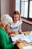 Het richten van vrijwilligers het becommentariëren achterstallig leningsbericht aan bejaard mevrouw stock fotografie