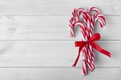Het riet van het Kerstmissuikergoed op een witte houten lijst stock afbeeldingen