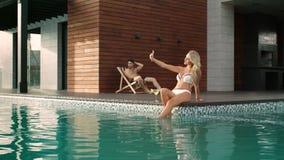 Het rijke paar ontspannen dichtbij pool bij luxehuis Sexy vrouw die selfie foto nemen stock video