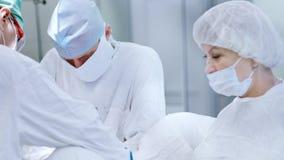 Het rijpe chirurg dragen maskeert en witte eenvormig tijdens werken omringd door medisch personeel stock footage