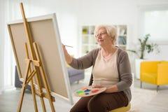 Het rijpe dame schilderen op een canvas stock fotografie