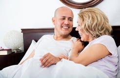 Het rijpe het houden van paar lounging in bed na het awaking van geknuffel royalty-vrije stock afbeelding