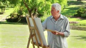 Het rijpe kunstenaar schilderen op een canvas stock videobeelden