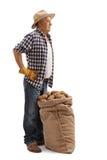 Het rijpe landbouwer stellen met het hoogtepunt van de jutezak van aardappels stock afbeelding
