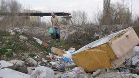 Het rijpe mannelijke reinigen voor plastiek bij afvalplaats stock video