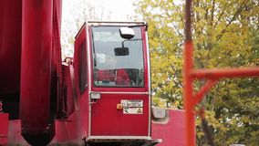 Het rijpe mannetje in rood eenvormig en GLB zit in rode kraancabine en stelt het in werking stock videobeelden