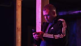 Het rijpe mannetje in sport Jersey houdt smartphone binnen donkere zaal indient stock footage