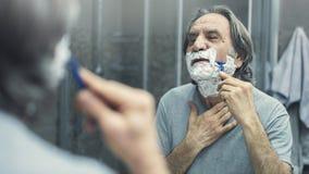 Het rijpe mens scheren voor spiegel stock afbeeldingen