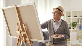 Het rijpe mens schilderen op een canvas met een penseel stock footage