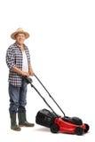 Het rijpe mens stellen met een rode grasmaaimachine Stock Foto