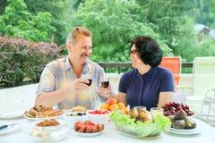 Het rijpe paar bekijkt elkaar en gerinkelglazen wijn Stock Afbeelding