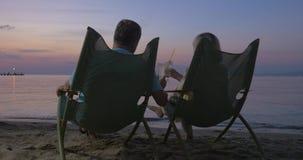 Het rijpe paar ontspannen op de strand en het drinken cocktails stock videobeelden