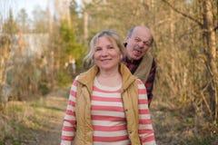 Het rijpe vrouw glimlachen die zich openlucht bevinden Haar echtgenoot die haar plagen die tong tonen stock foto's