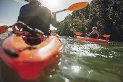 Het rijpe vrouw kayaking in meer op een zonnige dag Stock Afbeelding