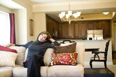Het rijpe vrouw ontspannen op woonkamerbank royalty-vrije stock foto
