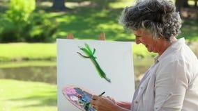 Het rijpe vrouw schilderen op een canvas stock videobeelden