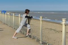 Het rijpe vrouw streching door het strand Stock Afbeeldingen