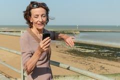 Het rijpe Vrouw texting op het strand Royalty-vrije Stock Afbeeldingen