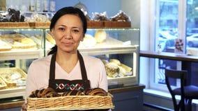 Het rijpe vrouwelijke bakker stellen bij haar opslag met een mandhoogtepunt van croissants stock video