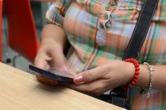 Het rijpe vrouwen` s hand texting op smartphone bij restaurant stock foto's