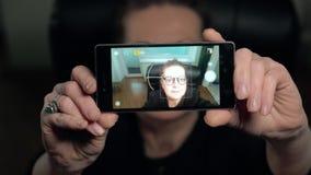 Het rijpe vrouwenbrunette in glazen maakt selfy zitting als voorzitter stock footage