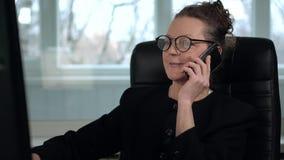 Het rijpe vrouwenbrunette in glazen werkt aan computer en neemt een telefoongesprek met glimlach stock video