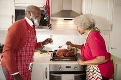 Het rijpe zwarte paar die Kerstmisdiner in hun keuken voorbereiden, mens die een glas opheffen als zijn vrouw bedruipt het braads stock foto's