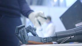 Het robo-wapen herhaalt de bewegingen van de menselijke hand Het plastic wapen van een robot wordt gebogen als een menselijke han stock videobeelden