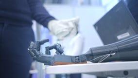 Het robo-wapen herhaalt de bewegingen van de menselijke hand Het plastic wapen van een robot wordt gebogen als een menselijke han stock video