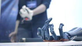Het robo-wapen herhaalt de bewegingen van de menselijke hand Het plastic wapen van een robot wordt gebogen als een menselijke han stock footage
