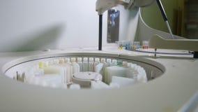 Het robotachtige materiaal zet Medische Steekproeven op de Transportbandlijn Chemie, geneesmiddel, medische apparatuur Sluit omho stock videobeelden