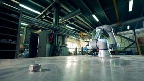 Het robotachtige wapen beweegt toestellen op een lijst bij een fabriek stock footage