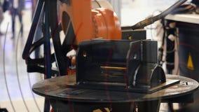 Het robotlassen last assemblage automobieldeel bij de tentoonstelling media Tentoonstelling van high-tech machines stock video