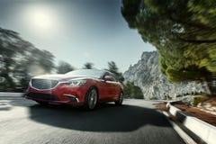 Het rode auto snelle snelheid drijven op asfaltweg dichtbij berg bij dag Stock Foto's