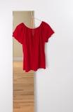 Het rode blouse hangen op een spiegel Royalty-vrije Stock Foto's
