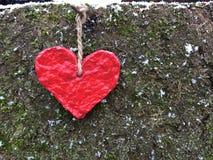 Het rode document hart hangt op de speld op een rustieke achtergrond stock afbeelding