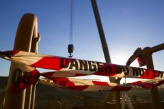 Het rode en witte de bandteken van de gevaarsmarkering bij uitsluitingsstreek het vastbinden van werkplaats liet vallen objecten  royalty-vrije stock afbeeldingen
