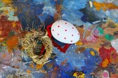 Het rode en witte ei van Pasen op oud kleurrijk artistiek houten palet royalty-vrije stock fotografie
