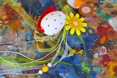 Het rode en witte ei van Pasen op oud kleurrijk artistiek houten palet royalty-vrije stock afbeeldingen