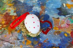 Het rode en witte ei van Pasen op oud kleurrijk artistiek houten palet royalty-vrije stock afbeelding
