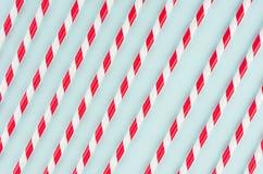Het rode gestreepte cocktailstro op pastelkleurmunt kleurt als abstracte blije achtergrond, diagonaal lijnenpatroon stock fotografie