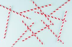 Het rode gestreepte cocktailstro op pastelkleurmunt kleurt als abstracte blije achtergrond, willekeurig patroon stock afbeelding