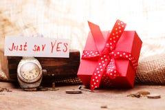 Het rode giftvakje bond rode lint en teksten stock afbeeldingen