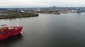 Het rode grote geladen de containerschip van de ladingsvracht komt bij stedelijke industriële haven in het verbazende hoogste 4k  stock footage