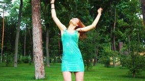 Het rode haired meisje in Holi-verven danst in groen park in langzame motie stock video