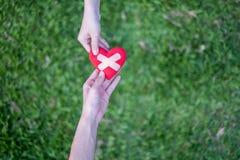 Het rode hart in de handen van de vrouw en de handen van de twee mannen wordt hersteld Het betekent het helpen moeilijke tijden i stock afbeeldingen