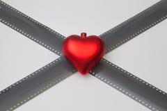 Het rode hart en de uitgerolde blootgestelde 35mm filmstroken Royalty-vrije Stock Afbeelding
