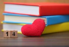 Het rode hart van de valentijnskaartendag met kleurrijke boeken op oud hout holida Royalty-vrije Stock Afbeeldingen